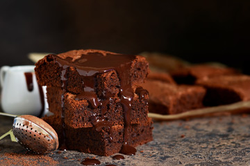 Brownie is a classic American dessert. Pie with chocolate sauce on a dark background.