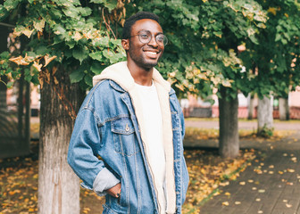 Wall Mural - Fashion smiling african man wearing jeans jacket, eyeglasses in autumn city park