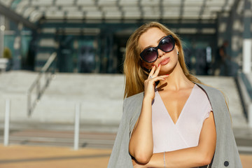 Magnificent young model in stylish sunglasses posing at the street in sunny evening. Space for text