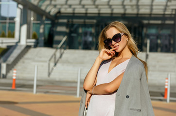 Sexy blonde lady in stylish sunglasses posing at the street in sunny evening. Space for text