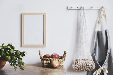 Vintage kitchen interior with mock up photo frame, straw basket, and kitchen accessories. Minimalistic concept of kitchen space.