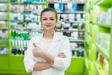 Attractive smiling woman pharmacist pose in drugstore
