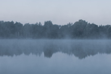 Gruseliger See mit Morgendunst im kühlen Blau. Standort: Deutschland, Nordrhein-Westfalen, Pröbstingsee