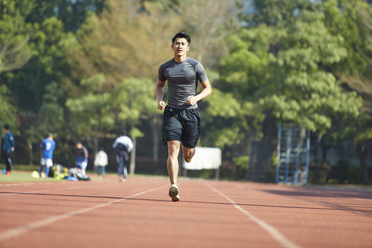 young asian male athlete running on track