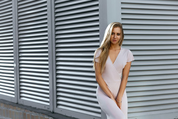 Seductive tanned model in fashionable outfit posing at the background of metal shutters. Space for text