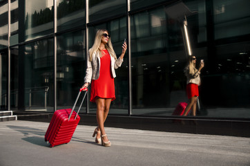 Attractive young businesswoman full length with suitcase looking at smartphone, modern building / airport in background