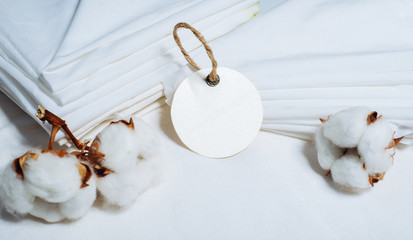 Round paper tag beside pile of fabrics and cottons balls. Mock up cotton template on white.