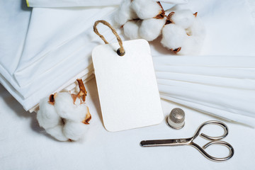 Rectangle paper tag beside pile of fabrics and cottons balls. Mock up cotton template on white.