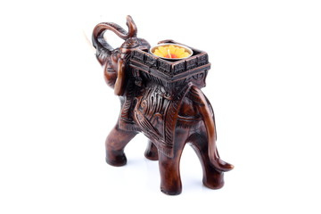 Brown Gold Black elephant made of resin like wooden carving with candle holder with white ivory. Stand on white background, Isolated, Art Model Thai Crafts, For decoration Like in the spa. Engraved pa