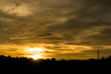 Airplane on the Electricity Pylon and beautiful sunset background