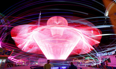 A long exposure shows a carousel at the traditional Knabenschiessen public festival in Zurich
