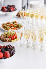 solemn happy new year banquet. Lot of glasses champagne or wine on the table in restaurant. buffet table with lots of delicious snacks. canapes, bruschetta, and little desserts on white plate