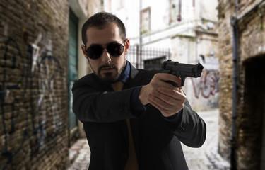 Mafia man or racketeer holds pistol in hands.