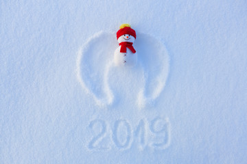 Snow angel with wings in red hat and scarf is laying on the snow. Writing 2019. Happy new year. Beautiful snowman.