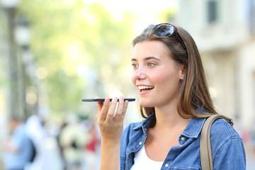 Girl using voice recognition of the phone in the street