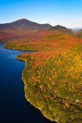 Fall colors surround a lake in New England - aerial