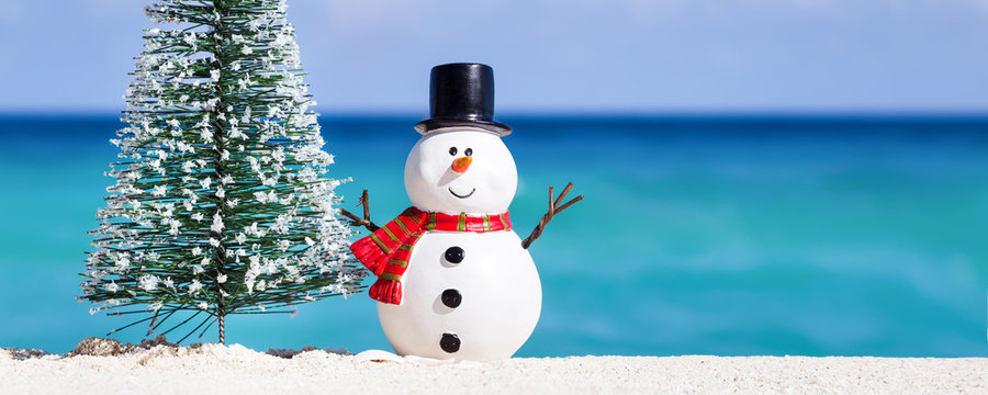 Snowman toy and fir tree at white sandy beach