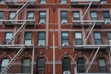 Brick building front with fire escapes and lampost in NYC