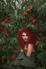 Fairy lady with red curly hair in a peach orchard hiding among the branches