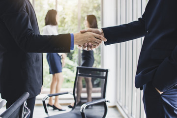Successful negotiate or corporation of partnership, business people hands shake in meeting room