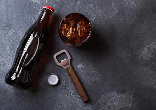 Bottle of cola soda drink and glass with ice cubes next to opener on black stone background.