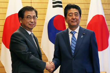 Japan's Prime Minister Shinzo Abe shakes hands with South Korea's National Intelligence Service chief Suh Hoon before their meeting at Abe's official residence in Tokyo
