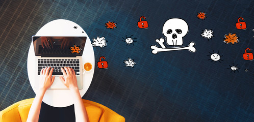 Virus and scam theme with person using a laptop on a white table