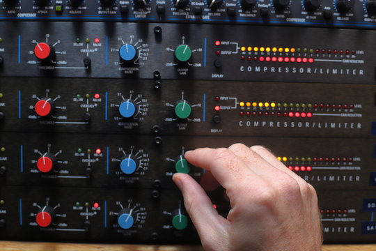 Hands adjusting knobs on sound compressors used for music production and broadcast audio