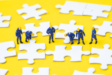 Teamwork help solving problem and solution metaphor concept, miniature people worker, staffs or employee help finishing jigsaw puzzle pieces on yellow background