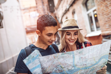 Cheerful casual couple traveling in city and using paper map to create route
