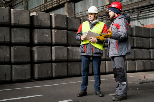 Full length  portrait of mature foreman wearing hardhat  giving instructions to worker while standing by concrete blocks in workshop, copy space