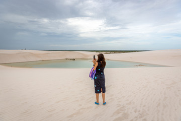 Young woman snapping a cellphone video at a cloudy day in the lencois maranhenses national park in Brazil