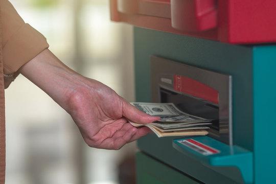 Closeup woman withdrawing the cash via ATM, business Automatic Teller Machine concept