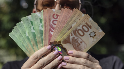 A Woman Fanning Out Canadian Cash