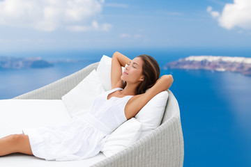 Wall Mural - Luxury home lifestyle woman relaxing on comfortable outdoor sofa daybed chair sleeping sun tanning breathing fresh air on ocean background. Asian girl in comfort.