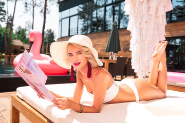 Perfect style. Smart beautiful woman looking at you while lying on the beach bed with a magazine
