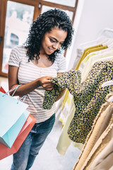 Young black woman exploring textile of modern blouse on hangers while shopping alone