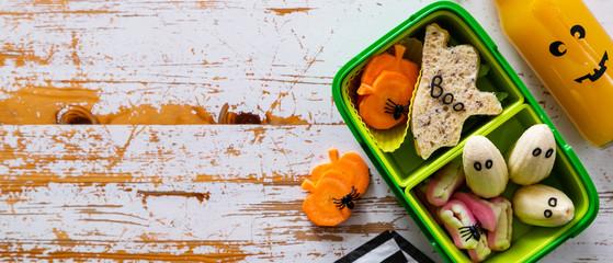 Halloween style school lunch box - ghost sandwich, pumpkin carrots, bananas, juice, top view
