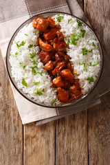 Stewed Bourbon chicken in sauce with whiskey, sugar, ginger and soy, served with rice on a plate. Vertical top view