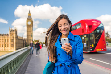 London phone business woman texting on smartphone mobile app for payment or online shopping. Urban city lifestyle Asian girl happy walking on Big Ben and red bus background.