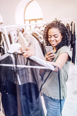Smiling black woman in shop taking photo of trendy outfit on hanger