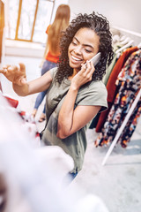 Cheerful casual black woman speaking on smartphone happily while choosing outfit in shop