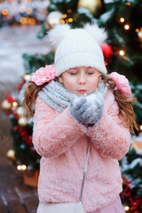 happy child girl playing outdoor on the walk in snowy winter city decorated for new year holidays. Trees with christmas lights on background
