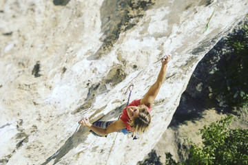Young female rock climber on a cliff face.