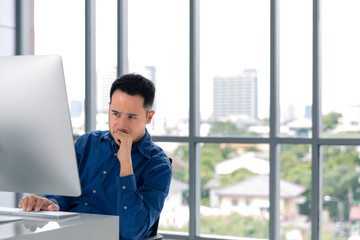 Young Asian businessman looking at the computer screen. His face expression was concerned with his work in modern office with large windows as background.
