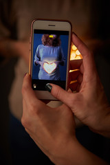 Women hands holding smartphone with the image of a girl with a heart in her hands.