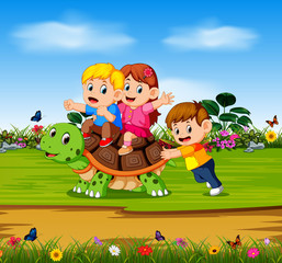 the three children are playing on the big turtle in the forest