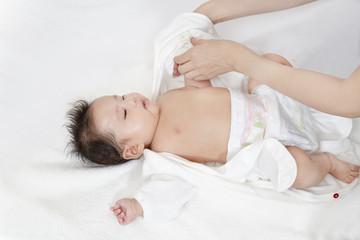 新生児の沐浴後に服を着せる方法を説明するマニュアル用写真、寝た赤ちゃんに白いロンパースを着せる手順イメージ