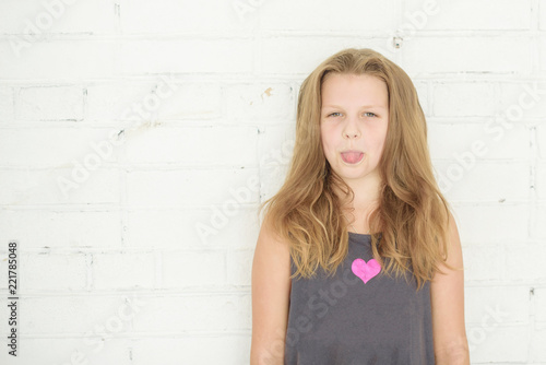 pre teen girl teen girl puts out tongue on white brick wall