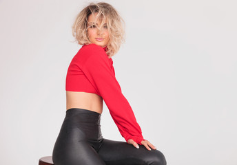 attractive woman in red top with blonde messy hair sitting